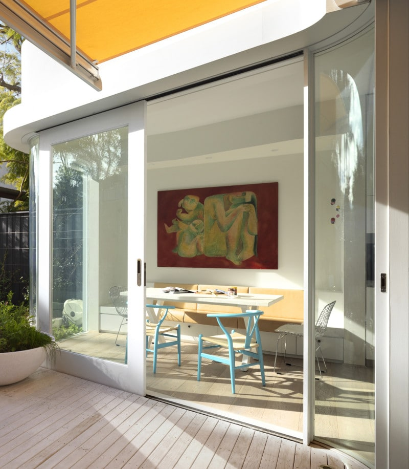 Recessed White Timber Framed Sliding Doors, Curved Awning Curved Glass Wall, Timber Deck, Concrete