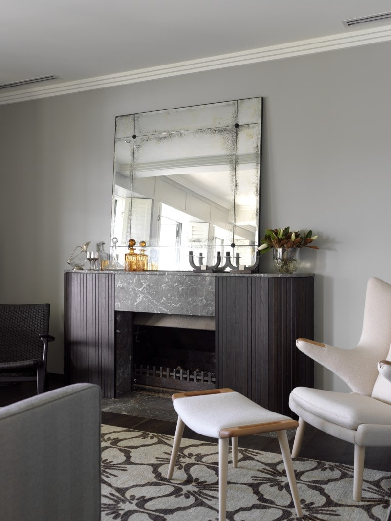 rounded dark stained timber panel and marble mantel