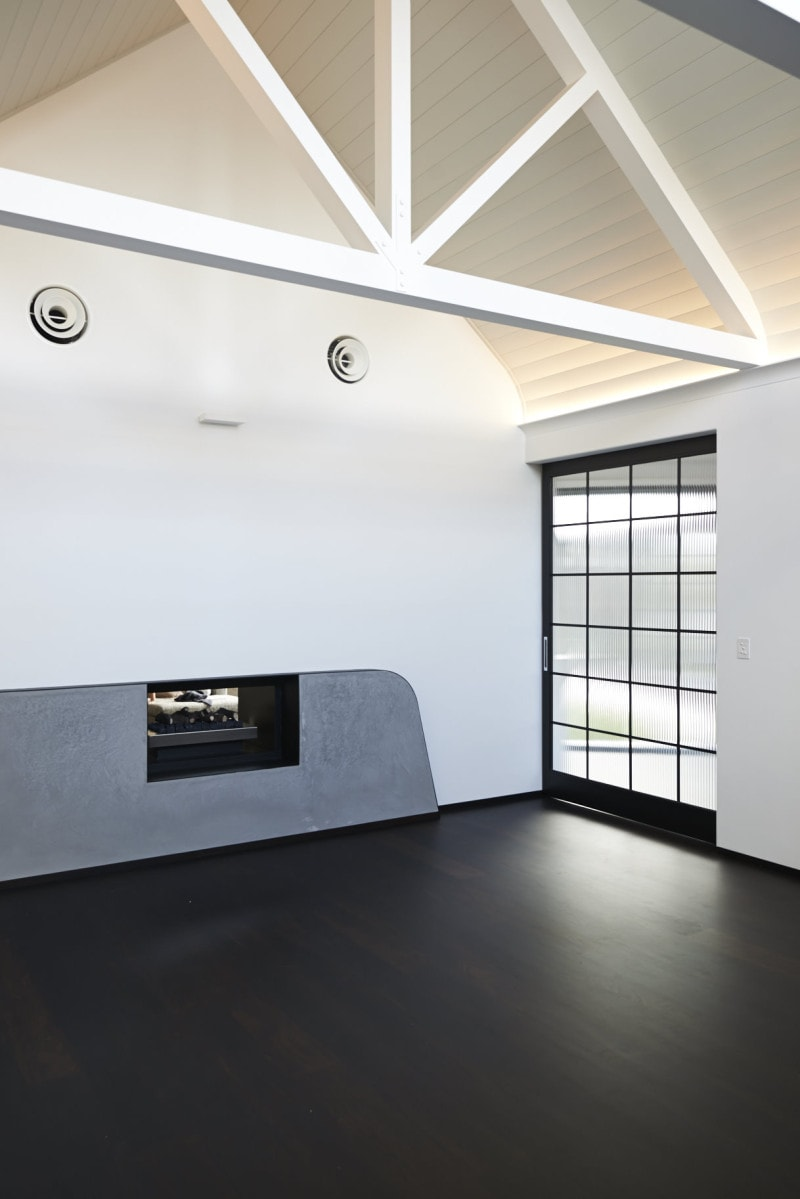 Polished Concrete Gas fireplace, White Timber Panel Lined, Raked Ceiling, White Exposed Timber Trusses, Fireplace, Thin Steel Glazed Doors