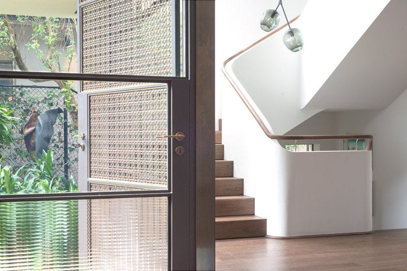 light filled stairwell and woven brass entry door