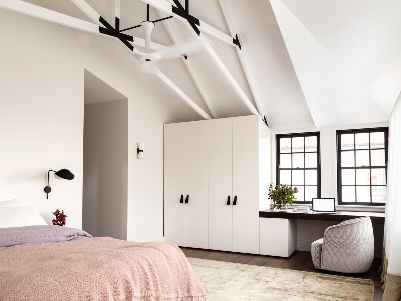 light filled bedroom with exposed rafters and steel reinforced trusses