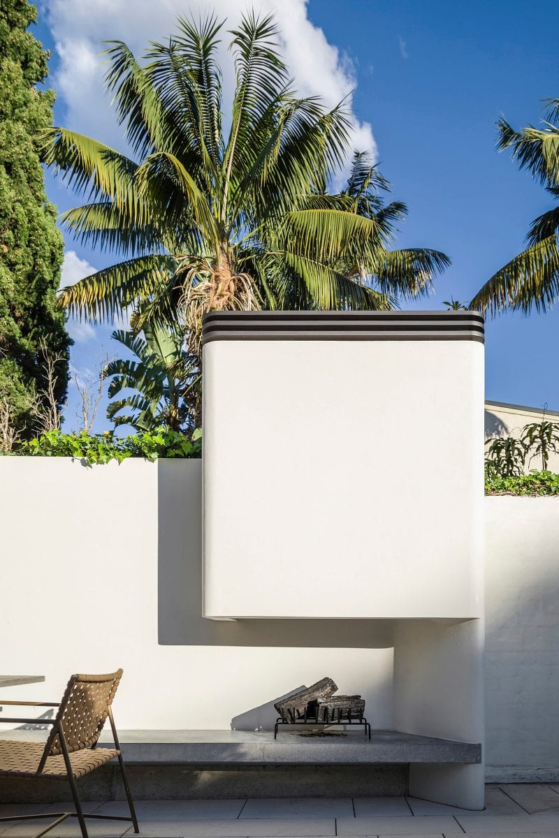 Luigi Rosselli Architects | Woollahra terrace house internal courtyard with outdoor fireplace, concrete bench and palms