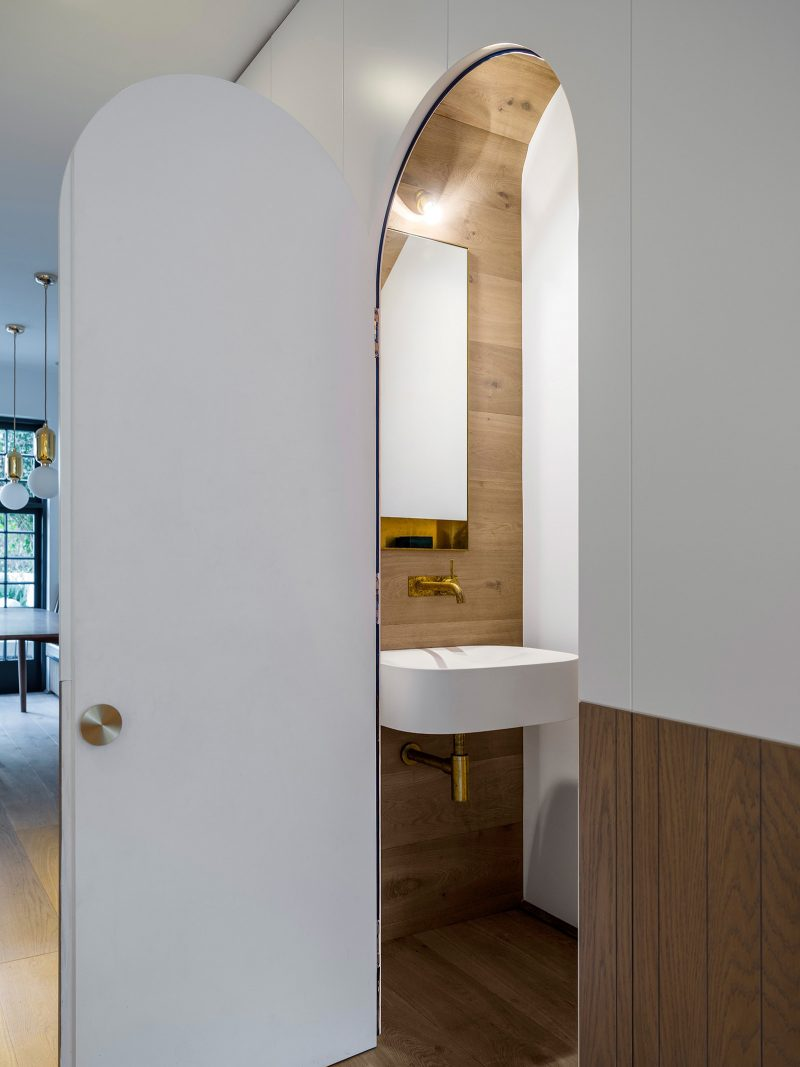 Luigi Rosselli Architects | Terrace under stair powder room with arched door, curved timber ceiling, and brass tap