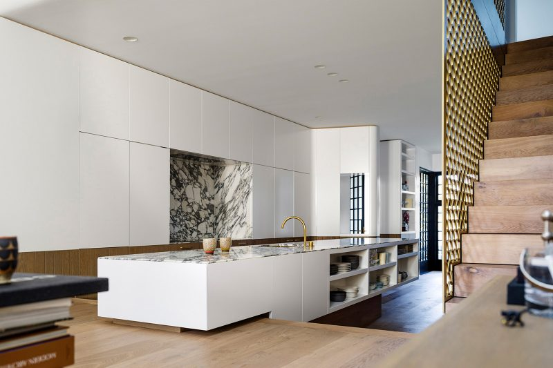 Luigi Rosselli Architects | split level kitchen with carrara marble bench top kitchen island, timber flooring and brass screen