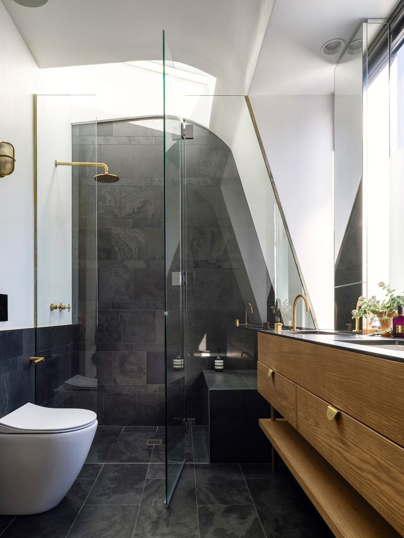 curved ceiling master ensuite with skylight brass shower dark slate tiles