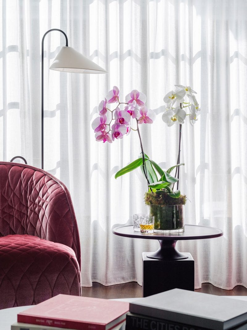 Luigi Rosselli Architects | Interior design with pink armchair, sheer curtains, books, pink flowers