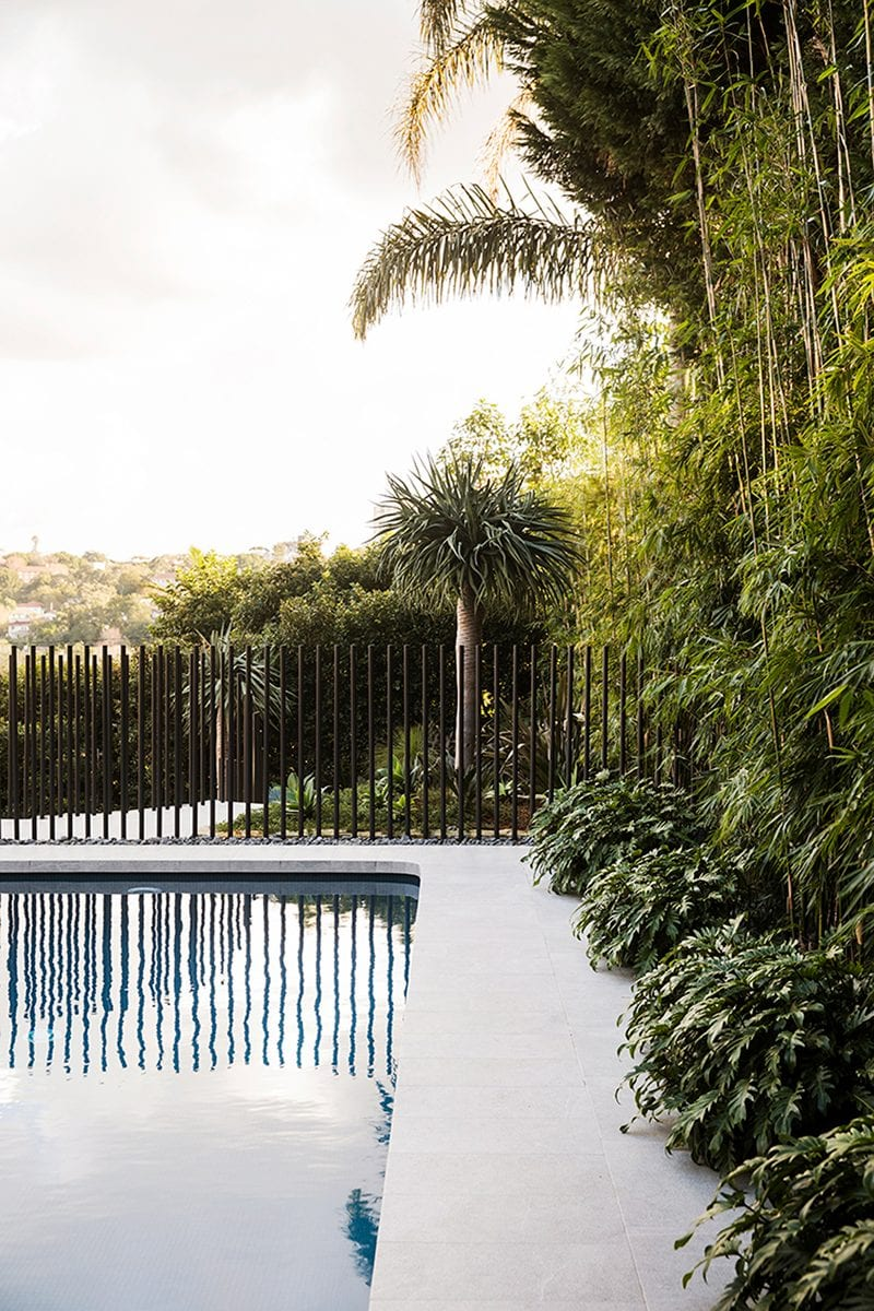 Luigi Rosselli Architects | Pool terrace with reflection, tropical landscaping and picket fence