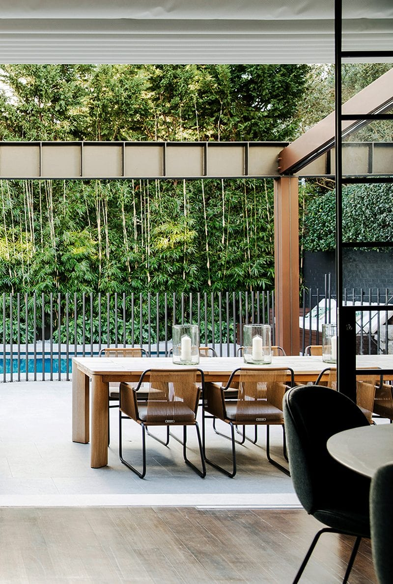 Luigi Rosselli Architects | Outdoor dining pool terrace with steel pergola beam, picket fence and bamboo landscaping