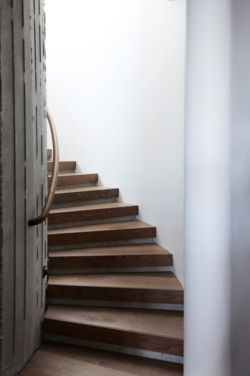 Luigi Rosselli Architects elliptically shaped stairwell in off form concrete, oak timber and smooth set plaster bathed in natural light