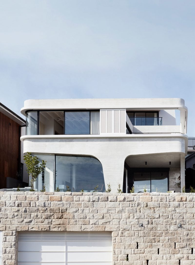 Luigi Rosselli designed Tamas Tee House Tamarama beach house with stone retaining wall, exposed off form concrete design, aluminium windows and custom cnc timber shutters