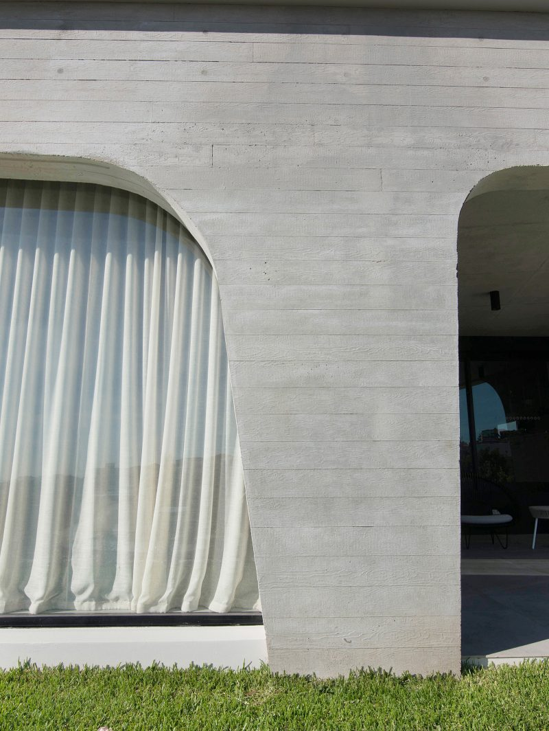 Luigi Rosselli designed tamas tee house with concrete with off-white cement curved window design