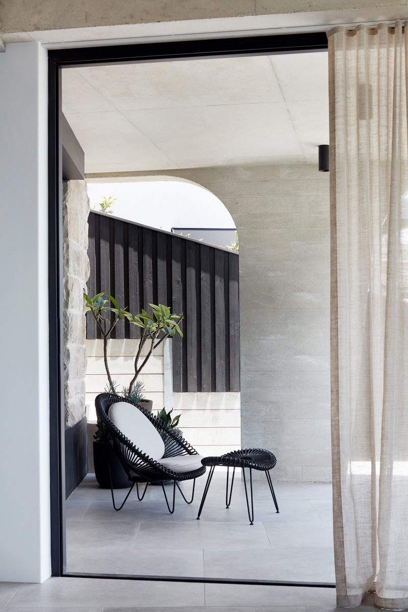 Reflective cement coloured vitrified ceramic tiles of the Luigi Rosselli designed tamas tee house covered terrace with concrete roof and pillar.