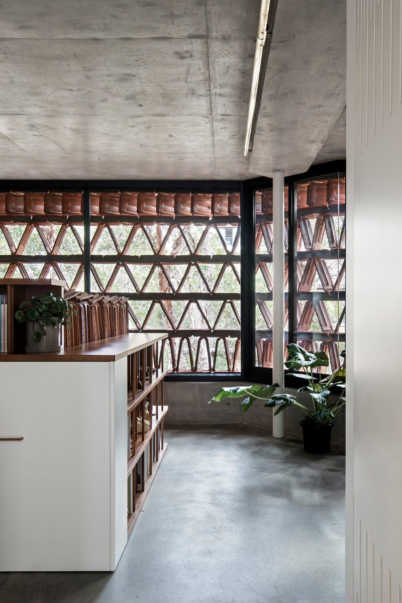 Luigi Rosselli Architects The Beehive studios interior with old terracotta roof tiles re-purposed to form the 'pigeon hole' bookshelf, indoor planting, concrete floor and Triangular Terracotta Facade Design