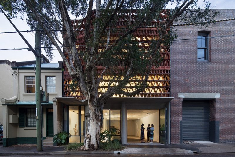 Luigi Rosselli Architects The Beehive Exterior streetscape at night with illuminated terracotta facade, Steel Doors, Boarded Concrete Awning, Cement Render