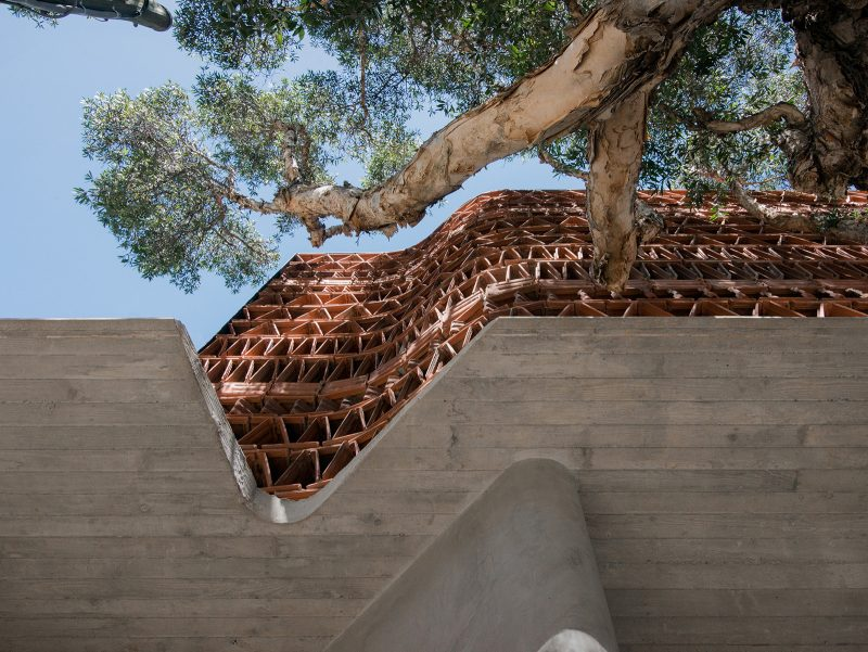 Luigi Rosselli ArchitectsThe Beehive studio with smooth Rockcote Acrylic Cement Render column, Boarded Concrete Awning, and Triangular Terracotta Facade Design