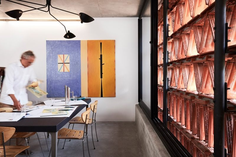 Luigi Rosselli Architects The Beehive studios' in Surry Hills interior with stainless steel and bent plywood Luigi Rosselli designed chairs, Serge Mouille pendant light and recycled Terracotta Facade in triangular pattern