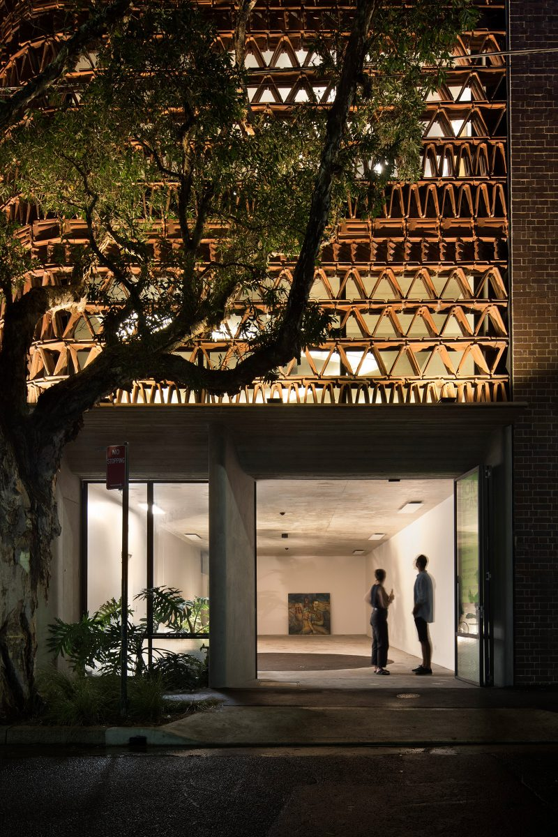 Luigi Rosselli Architects designed workspace The Beehive in evening with illuminated recycled terracotta facade, Monstera garden and paperbark tree